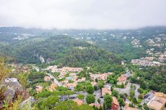 Daylight foggy view to Eze, Cote d`Azur village with medieval ho. Daylight foggy view to Eze, France Cote d`Azur village with medieval houses, roads and green stock images