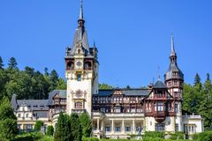 Daylight front view to ornamented facade of Peles castle. With tower and bright blue sky with clouds. Romanian kings summer residence in Carpathian Mountains Royalty Free Stock Photography