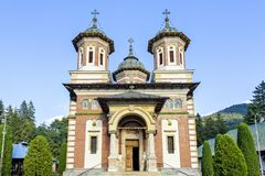 Daylight front view to Orthodox church of the Sinaia monastery. In Romania. Green trees and bright blue clear sky on background. Negative copy space, place for stock image