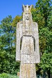 Daylight portrait view to Neagoe Basarab religious monument. And stone statue in monastery park. Trees and bright sky on background. Curtea de Arges, Romania Stock Photo