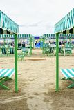 Daylight view to vibrant green sunchairs and sunshades on beach. Daylight portrait view to vibrant green sunchairs and sunshades on beach. Cloudy sky on Stock Images