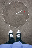 Daylight Saving Time on asphalt with two shoes, high angle from Royalty Free Stock Images