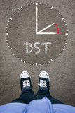 Daylight Saving Time on asphalt with two shoes, high angle from Royalty Free Stock Photos