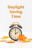 Daylight Saving Time. Black retro alarm clock and autumn leaves reminder to turn back clocks Royalty Free Stock Images