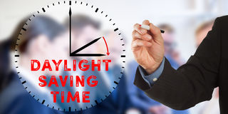 Daylight Saving Time, Business man hand writing with team. Daylight Saving Time, Male hand in business wear holding a thick pen, writing on an imaginary screen royalty free stock image