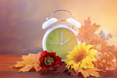 Daylight Saving Time Clock Concept. Autumn daylight saving time concept with green clock on natural wood table with sunset sky background, and added vintage royalty free stock photo