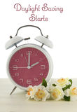 Daylight Saving Time concept. With spring theme pink retro style alarm clock on white wood background stock image