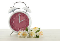 Daylight Saving Time concept with spring theme. Pink retro style alarm clock on white wood background royalty free stock photos