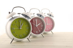 Daylight Saving Time concept. With three colorful retro style alarm clocks on white wood background stock photos