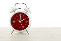 Daylight Saving Time with retro style alarm clock. With red face on white wood background royalty free stock photo