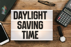 Daylight Saving Time in vintage style light box on office deskt. Op, high angle birds eye view Stock Photography