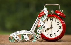 Daylight savings and time concept. Daylight savings concept - red alarm clock and tape measure with blank, copy space stock photo