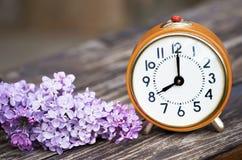 Daylight savings, spring forward concept. Orange alarm clock and purple lilac flowers royalty free stock image