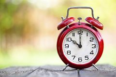Daylight savings time, autumn concept. Red alarm clock with copy space stock photos