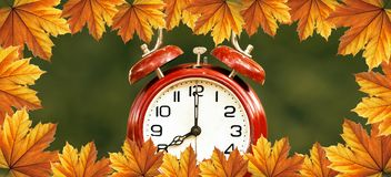 Daylight savings time in autumn - web banner. Daylight savings time, autumn concept - red alarm clock with orange leaves border - web banner idea royalty free stock photos