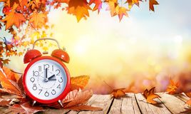 Daylight Savings Time Concept - Clock And Leaves. On Wooden Table royalty free stock images