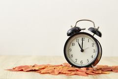 Daylight Savings Time Concept. Time for Autumn Clock And Leaves On Wooden Table with copy-space stock photo