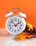 Daylight savings time ends in autumn fall with clock. Concept on orange background royalty free stock photography