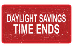 Daylight savings time ends. Red grunge sign with white text graphics daylight savings time ends Stock Photos