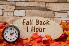 Daylight savings time message. Some fall leaves, an alarm clock and wood plaque on weathered brick with text Fall Back 1 hour Stock Image