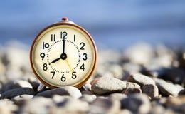 Daylight savings time, retro alarm clock. Daylight savings time concept, retro alarm clock standing on the beach stock images