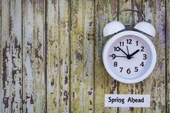Daylight Savings Time Spring Ahead concept top down view with white clock. Daylight Savings Time Spring concept top down view with white clock on wooden board Stock Image