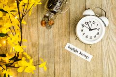 Daylight Savings Time Spring concept top down view. With white clock and yellow forsythia flowers on wooden board Stock Images