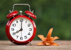 Daylight savings time, spring forward - banner of an alarm clock and flower. Daylight savings time, spring forward concept - web banner of a retro alarm clock royalty free stock images
