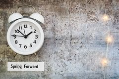 Daylight Savings Time Spring Forward concept top down view with white clock. Daylight Savings Time Spring concept top down view with white clock on gray board Royalty Free Stock Photos