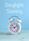 Daylight savings time white clock on a vintage aqua blue wood table Royalty Free Stock Photo