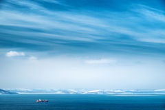 Daylight seascape. Daylight landscape with cargo ship and blue sky Royalty Free Stock Image