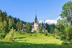 Daylight side far view to Peles castle front facade with hanging. Flag. Tree forest and bright blue clear sky on background. Romanian kings summer residence in Stock Photography