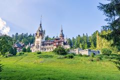 Daylight side far view to Peles castle front facade with hanging. Flag. Tree forest and bright blue clear sky on background. Romanian kings summer residence in Royalty Free Stock Photos