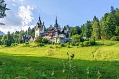 Daylight side far view to Peles castle front facade with hanging. Flag. Tree forest and bright blue clear sky on background. Romanian kings summer residence in Royalty Free Stock Photography