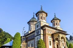 Daylight side view to Orthodox church of the Sinaia monastery. In Romania. Green trees and bright blue clear sky on background. Negative copy space, place for stock image
