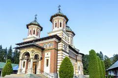 Daylight side view to Orthodox church of the Sinaia monastery. In Romania. Green trees and bright blue clear sky on background. Negative copy space, place for royalty free stock images