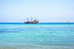 Daylight view from beachline to people watching two pirate ships stock image