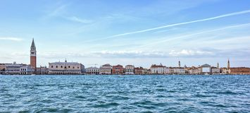 Daylight view from boat to Riva degli Schiavoni waterfront and c. Olorful tall buildings. Bright blue sky with plane traces and clouds. Negative copy space stock image
