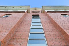 Daylight view from bottom to red brick facade of modern building. Bright blue sky on background stock images