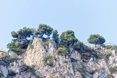Daylight view from bottom to rock mountains with green trees. And modern house yard on top. Bright blue clear sky. Negative copy space, place for text. Cap d` Stock Images