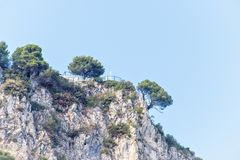 Daylight view from bottom to rock mountains with green trees. And modern house yard on top. Bright blue clear sky. Negative copy space, place for text. Cap d` Royalty Free Stock Photos