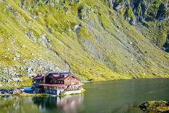 Daylight view to Balea Lake cottage with green mountains stock image