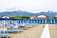Daylight view to beach with people resting on sunchairs. FORTE DEI MARMI, ITALY - JUNE 30, 2017: Daylight view to beach with people resting on sunchairs in a Royalty Free Stock Photo