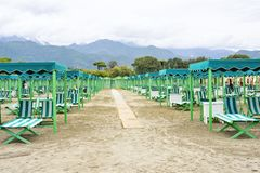 Daylight view to vibrant green sunchairs and sunshades on beach. Daylight view to beige sunchairs and sunshades on beach. Cloudy sky, buildings and mountains on Stock Images
