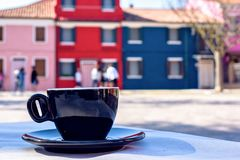 Daylight view to black coffee cup on table and colorful building. S with people walking on background. Bright blue clear sky. Negative copy space, place for text stock photo