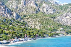 Daylight view to buildings near seashore, green trees and big ro. Ck mountains. Bright blue sky and water with yellow buoys. Cap d`Ail, France Royalty Free Stock Photo