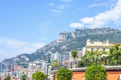 Daylight view to city buildings, green trees aligned, blue sky a. Nd big green mountains on background. Monaco, France Royalty Free Stock Images