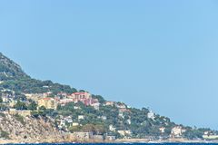 Daylight view to colorful buildings, trees and coastline of Cap. D`Ail, France. Bright blue clear sky. Negative copy space, place for text Royalty Free Stock Images