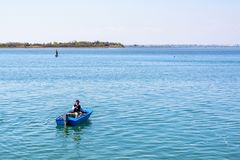 Daylight view to a fisherman in blue boat preparing fishing rod Stock Photos