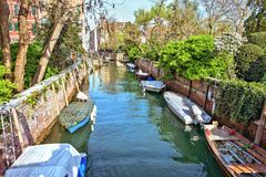 Daylight view to local canal with parked boats. Green trees and tall buildings on background. Bright blue sky with clouds reflecting on water. Venice, Italy stock image